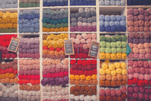 selection of differently colored yarn on shelves