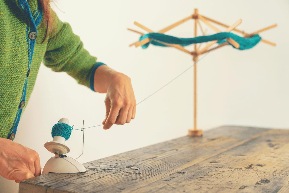 woman winding yarn with yarn swift
